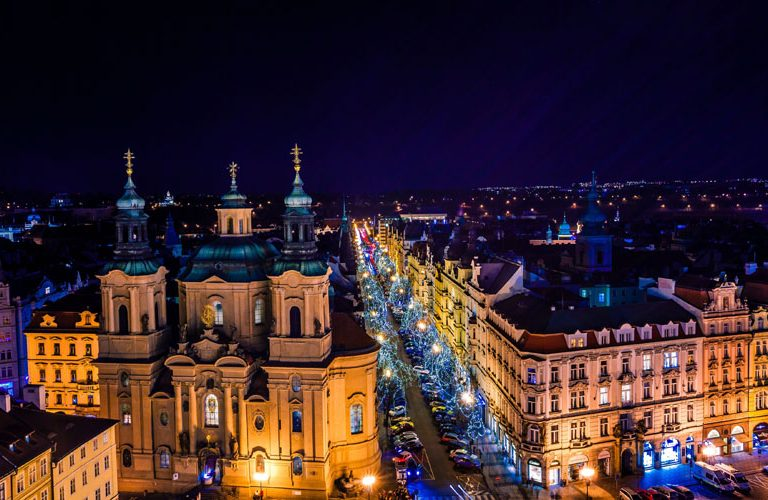 View of prague rooftops with the blue illuminated spires  in Old Town Prague, Czech Republich
