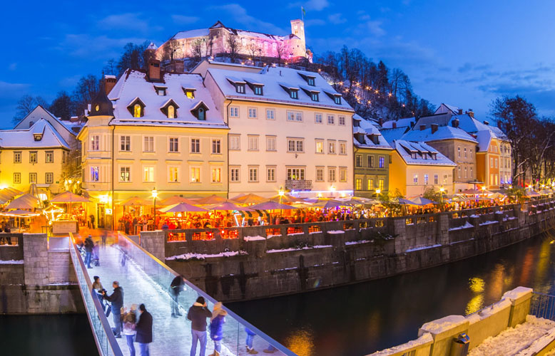 Ljubljana in Christmas time. Lively nightlife in old medieval city center decorated with Christmas lights. Slovenia, Europe. Shot at dusk with fish eye lens.