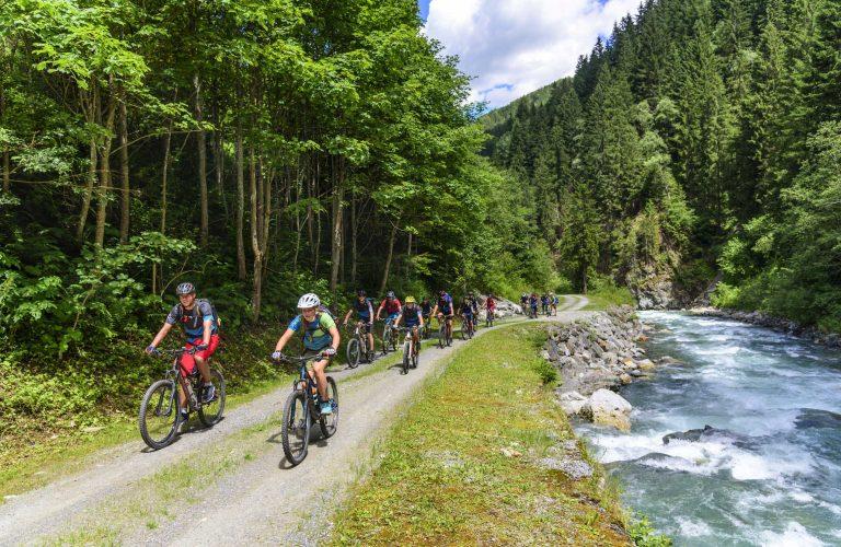 eine Gruppe Mountainbiker fhrt an einem Wildbach in den Alpen en
