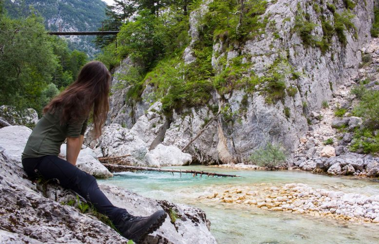 Girl sitting by the Soca river in Triglav national park, Sloveni