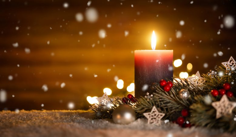 Burning candle, Christmas decoration and wooden background in falling snow, elegant low-key shot with festive mood