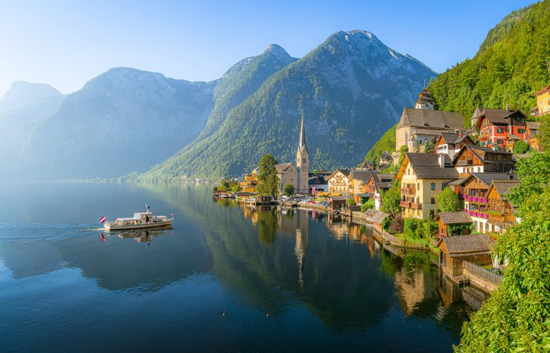 Classic panoramic view of idyllic Hallstatt lake in the Alps with famous old town with tourist ship in scenic golden morning light on a beautiful sunny day at sunrise in summer, Salzkammergut region, Austria